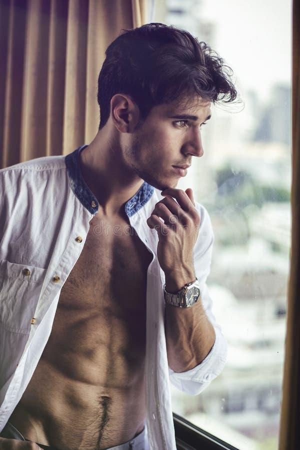 Homem novo 'sexy' com a camisa aberta na caixa muscular fotografia de stock royalty free
