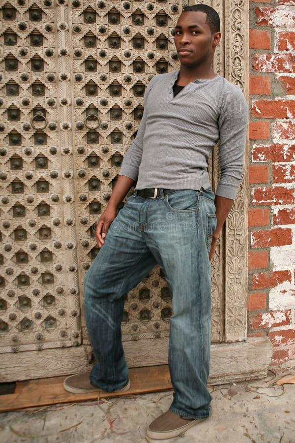 Homem novo 'sexy' do americano africano que inclina-se de encontro à GR fotos de stock royalty free