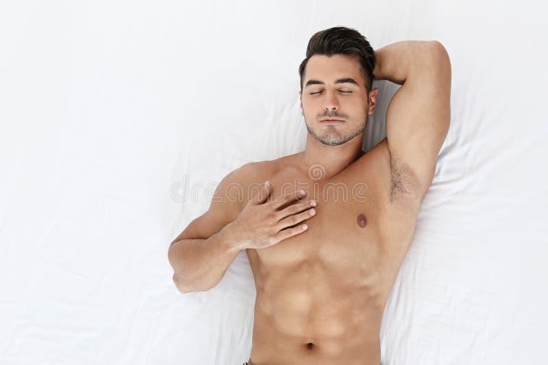Homem novo 'sexy' que dorme na cama macia fotografia de stock royalty free