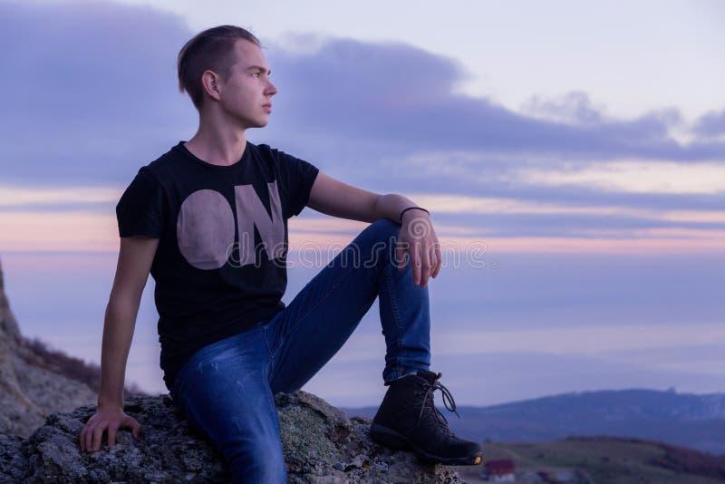 Homem novo situado com na parte superior das montanhas contra o contexto de um por do sol roxo, retrato no perfil imagem de stock royalty free