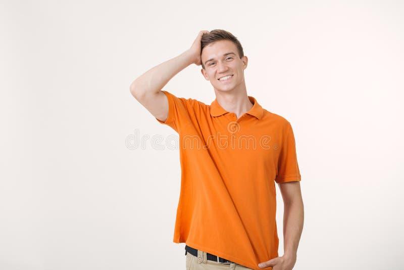 Homem novo surpreendido com cabelo marrom que sorri e que guarda sua mão na cabeça, sentimento excitado foto de stock