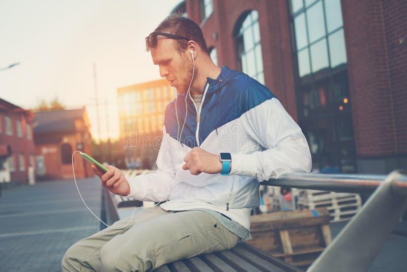 Homem novo surpreendido com o telefone celular e os auriculares que sentam-se no banco fotos de stock