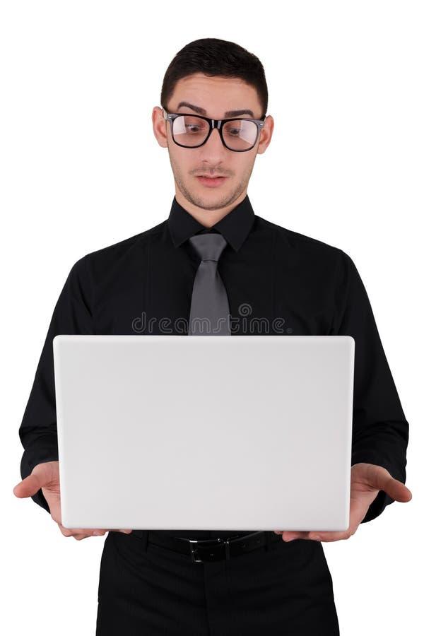 Homem novo surpreendido com os vidros que guardam o portátil fotografia de stock