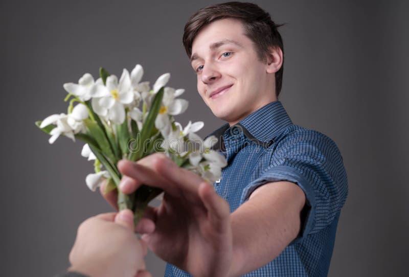 Homem novo surpreendido e de sorriso considerável que toma o ramalhete dos snowdrops imagens de stock