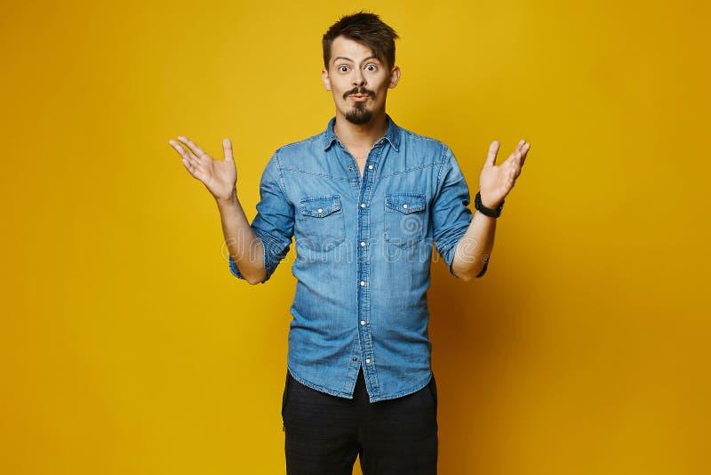 Homem novo surpreendido, moderno à moda com barba e bigode na camisa elegante das calças de brim no fundo amarelo, isolado fotos de stock royalty free