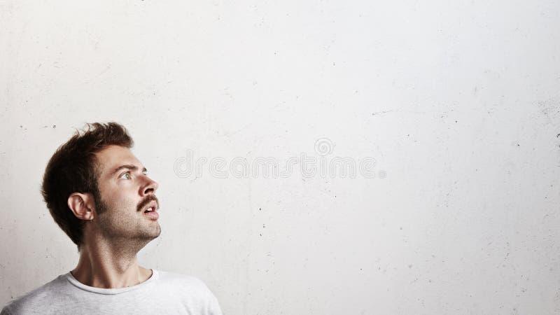 Homem novo surpreendido que olha acima fotografia de stock