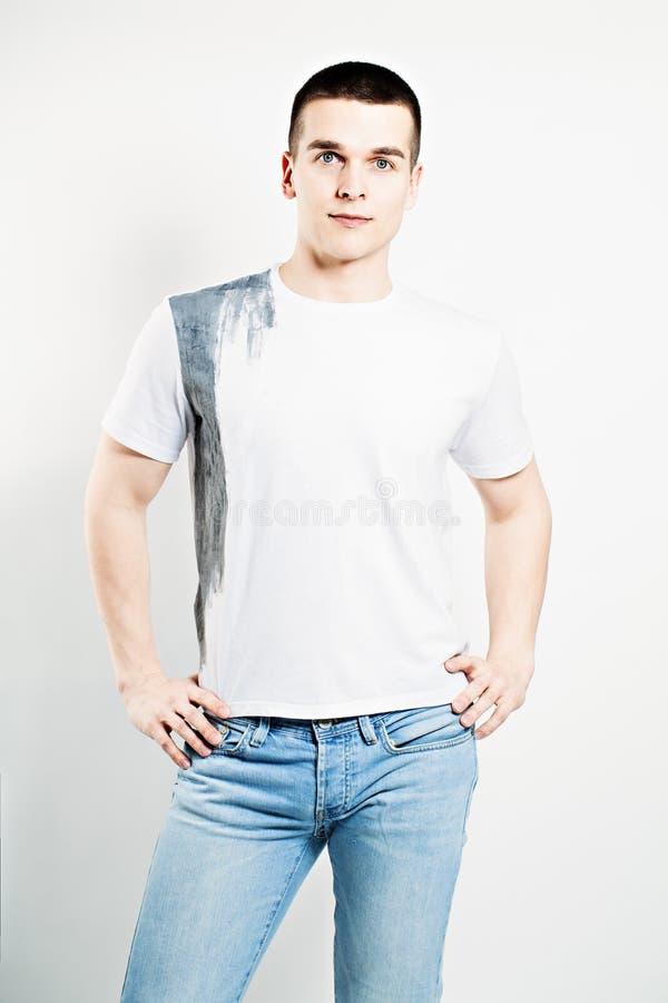 Homem novo T-shirt e calças de brim brancos imagem de stock royalty free
