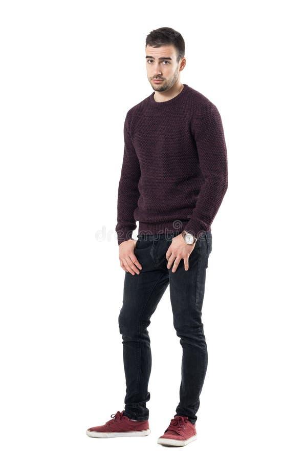 Homem novo triste com mãos em uns bolsos que vestem a camiseta que olha a câmera imagem de stock