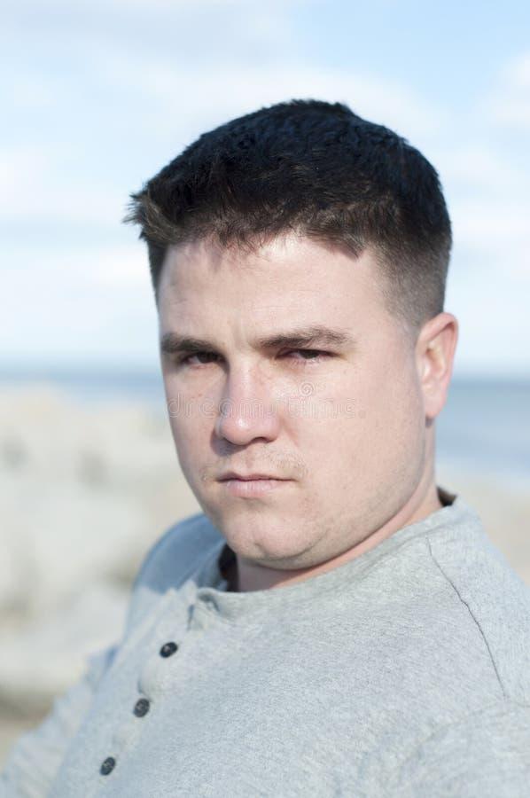 Homem novo triste na praia imagens de stock