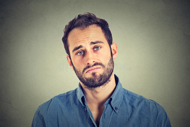 Homem novo triste no fundo cinzento da parede imagens de stock royalty free