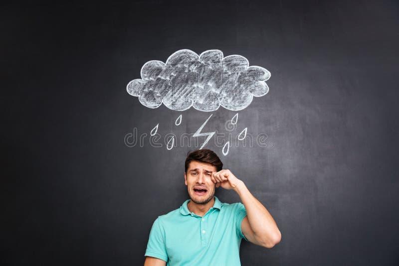 Homem novo triste que grita sobre o quadro-negro com raincloud tirado foto de stock
