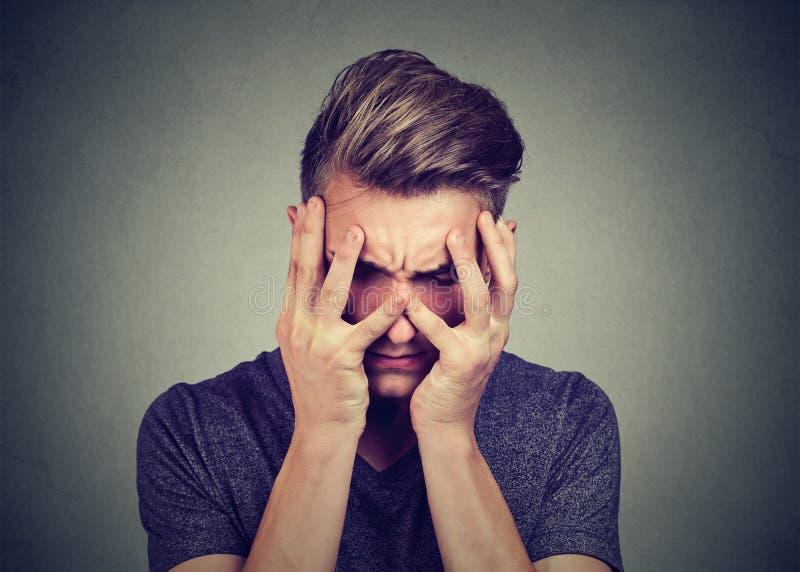 Homem novo triste que olha para baixo Conceito da depressão e da perturbação da ansiedade imagem de stock