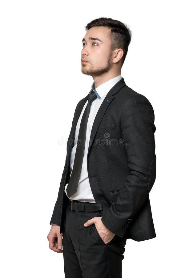 Homem novo um terno de negócio, mãos em seus bolsos, isolados no fundo branco imagens de stock royalty free