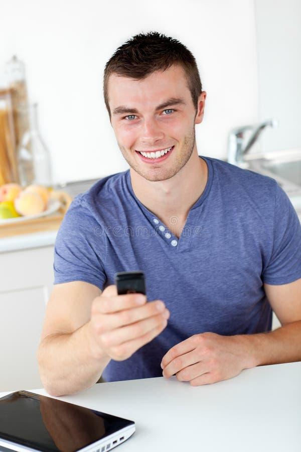 Homem novo vívido que emite um texto e um sorriso fotografia de stock royalty free