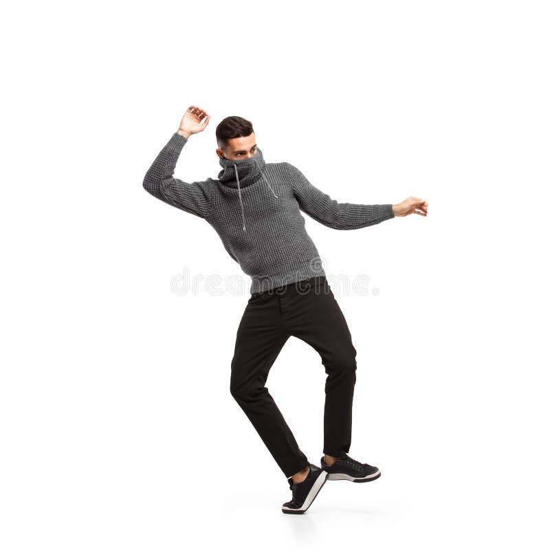 Homem novo vestido na gola alta cinzenta e em danças escuras das calças no fundo branco no estúdio fotografia de stock