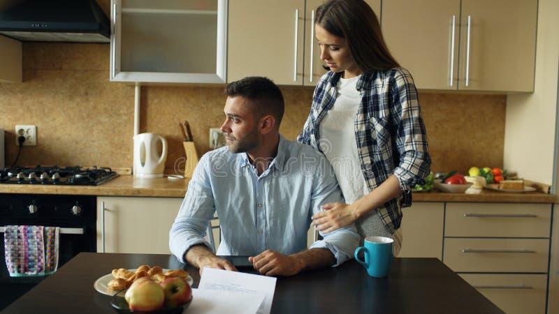 Homem novo virado que lê contas por pagar e abraçado por sua esposa que apoia o na cozinha em casa imagens de stock