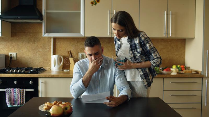 Homem novo virado que lê contas por pagar e abraçado por sua esposa que apoia o na cozinha em casa fotografia de stock royalty free