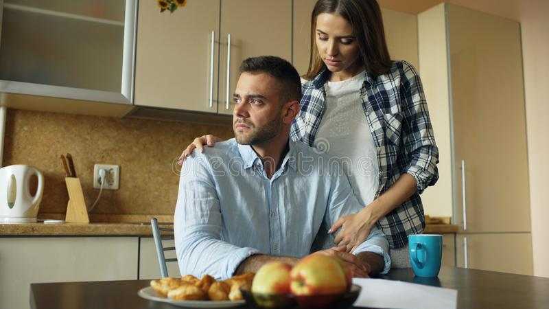 Homem novo virado que lê contas por pagar e abraçado por sua esposa que apoia o na cozinha em casa imagem de stock