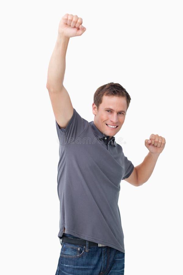 Homem novo vitorioso que aumenta o punho fotografia de stock
