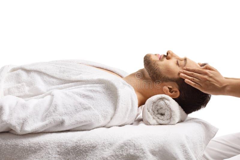 Homem num centro de spa a gozar de massagem na cabeça fotografia de stock royalty free