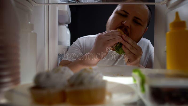 Homem obeso dedicado que come ansiosamente o hamburguer na noite, nutrição insalubre, dieta imagem de stock
