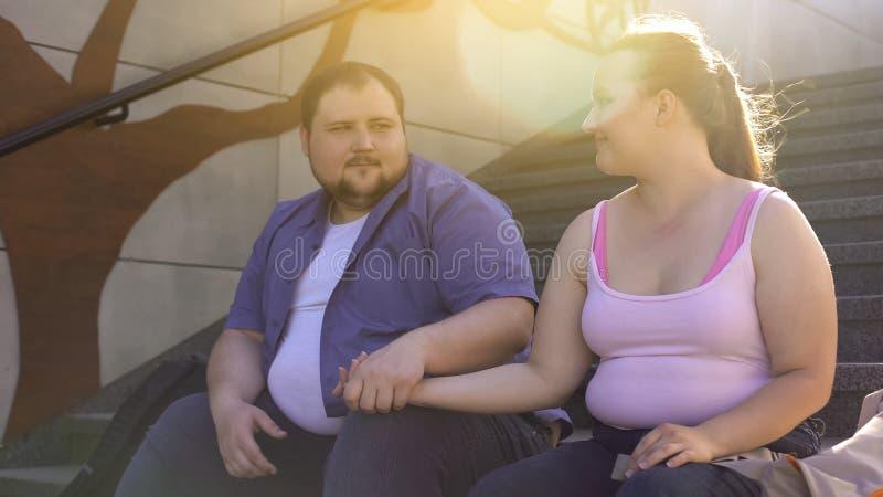 Homem obeso que guarda maciamente sua mão gorda da amiga, sentimentos verdadeiros, datando imagens de stock