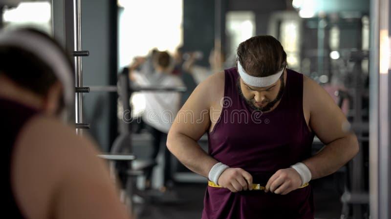 Homem obeso que mede a cintura gorda, verificando o resultado após a saúde de dieta e de formação fotografia de stock