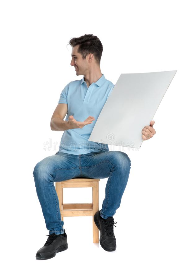 Homem ocasional alegre que apresenta um quadro de avisos e um sorriso vazios imagem de stock