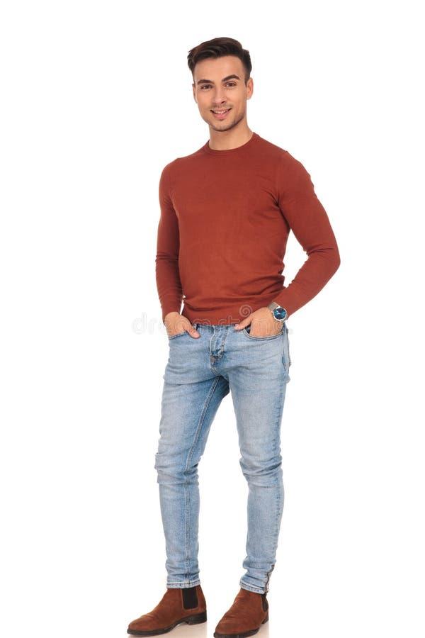 Homem ocasional apto de sorriso que está com mãos em uns bolsos imagens de stock