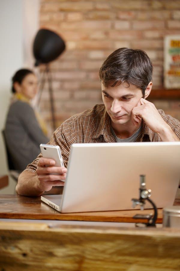 Homem ocasional com móbil e portátil fotografia de stock