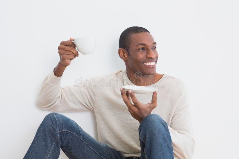 Homem ocasional do Afro que come o chá contra a parede fotografia de stock royalty free