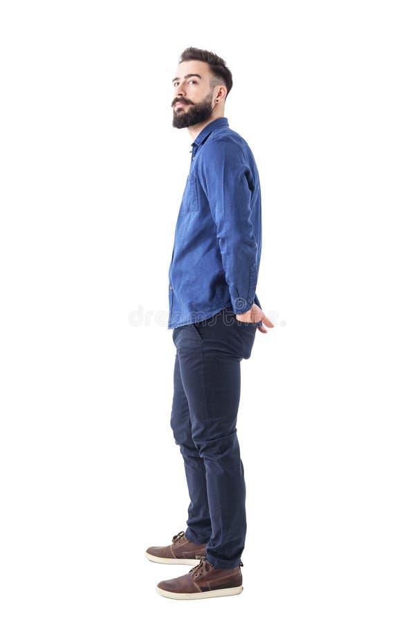 Homem ocasional esperto farpado à moda novo que olha acima com mãos em uns bolsos traseiros imagem de stock