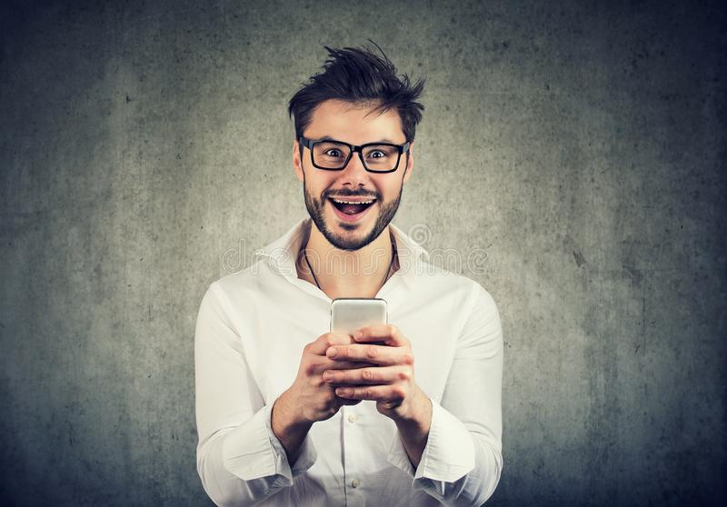 Homem ocasional farpado que olha o quando excitado usando o smartphone e olhando a câmera fotografia de stock