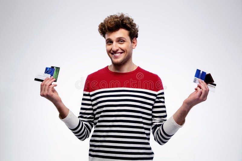 Homem ocasional feliz que guarda cartões de crédito foto de stock