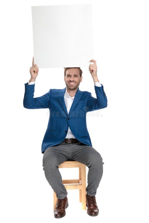 Homem ocasional feliz que guarda um quadro de avisos vazio acima de sua cabeça fotos de stock royalty free