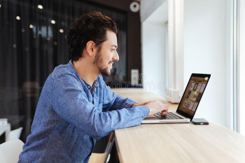Homem ocasional feliz que usa o portátil no escritório imagens de stock royalty free
