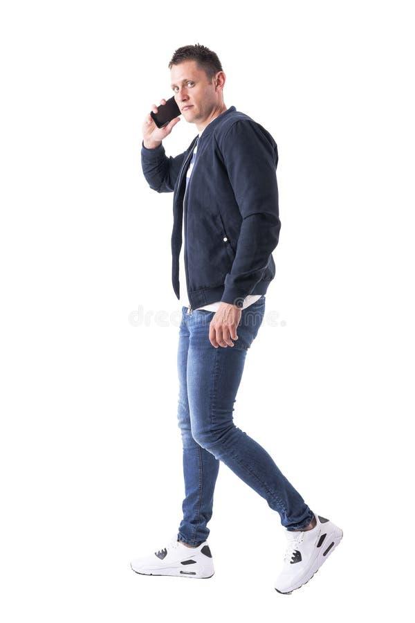 Homem ocasional macho sério seguro que fala no telefone que anda e que olha a câmera fotografia de stock
