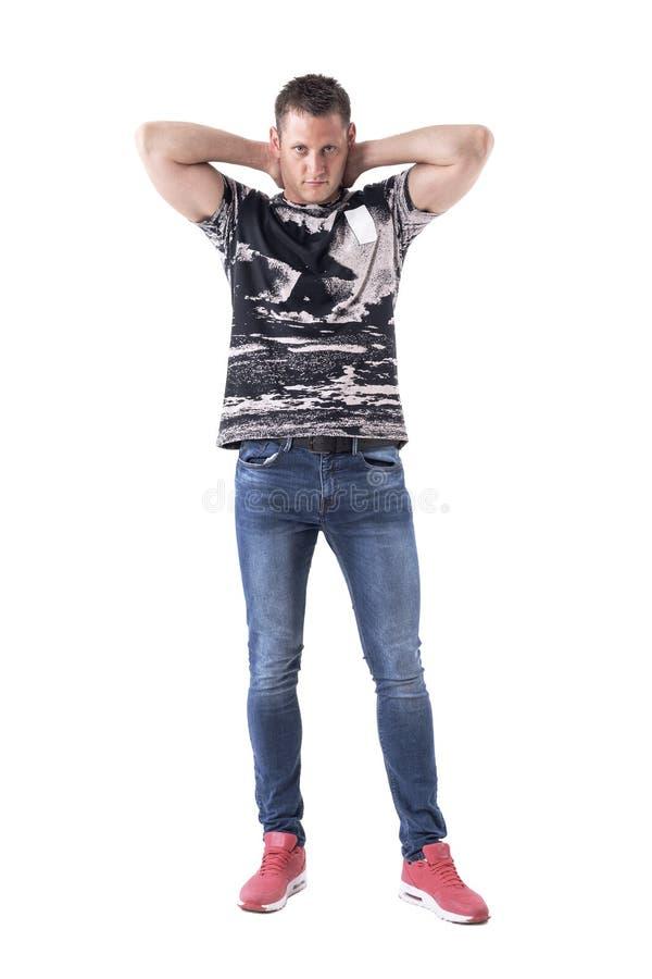 Homem ocasional muscular sério seguro que levanta com mãos atrás da cabeça foto de stock royalty free