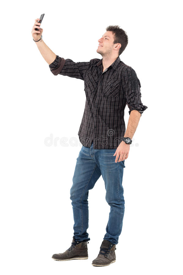 Homem ocasional nas calças de brim e na camisa de manta que tomam fotos com telefone celular imagens de stock