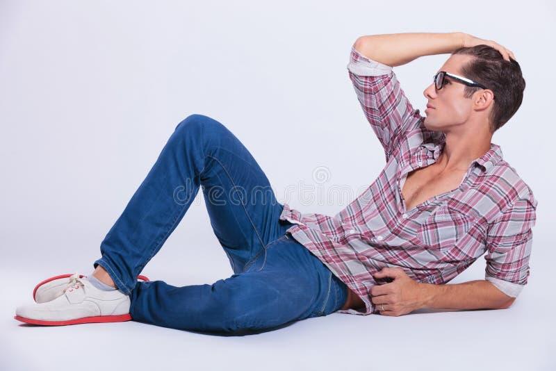 Homem ocasional no assoalho, mão das posses em seu cabelo imagens de stock