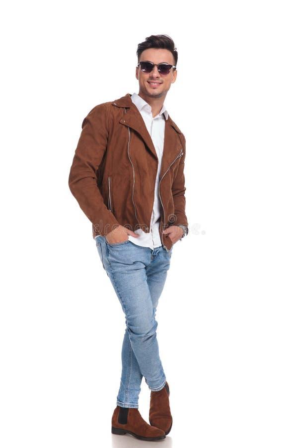 Homem ocasional no casaco de cabedal que está com mãos em uns bolsos imagens de stock