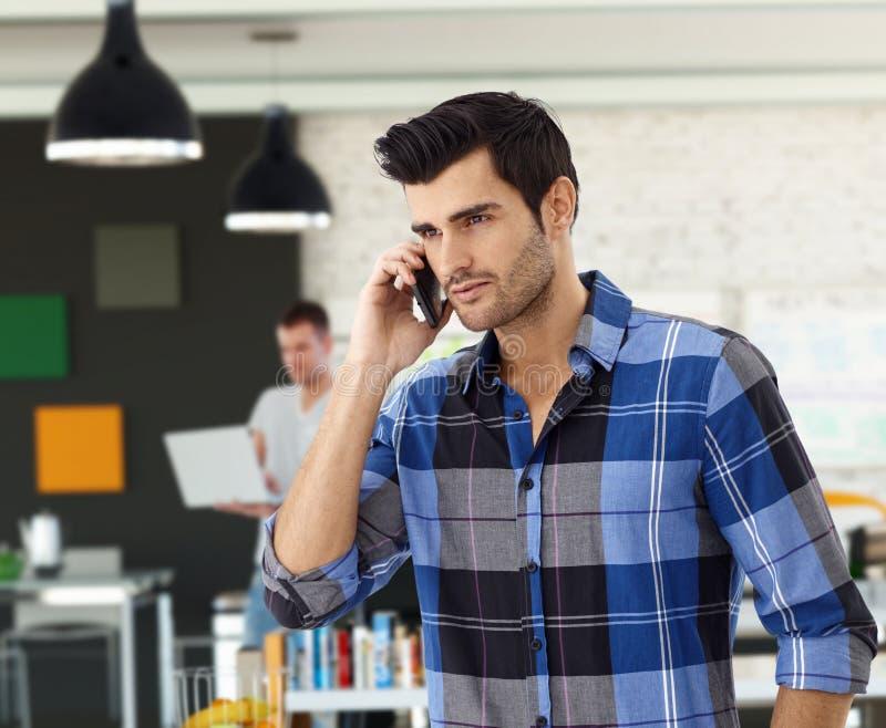 Homem ocasional no telefone no escritório foto de stock