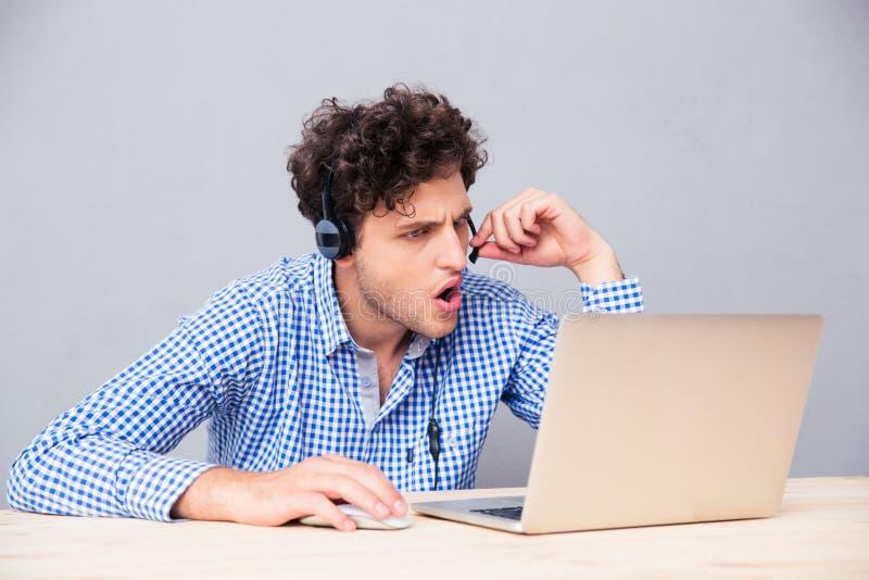 Homem ocasional nos haedphones usando o portátil imagens de stock