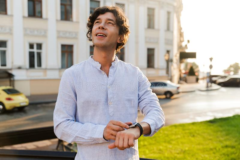 Homem ocasional novo alegre que ajusta seu relógio esperto fotos de stock royalty free