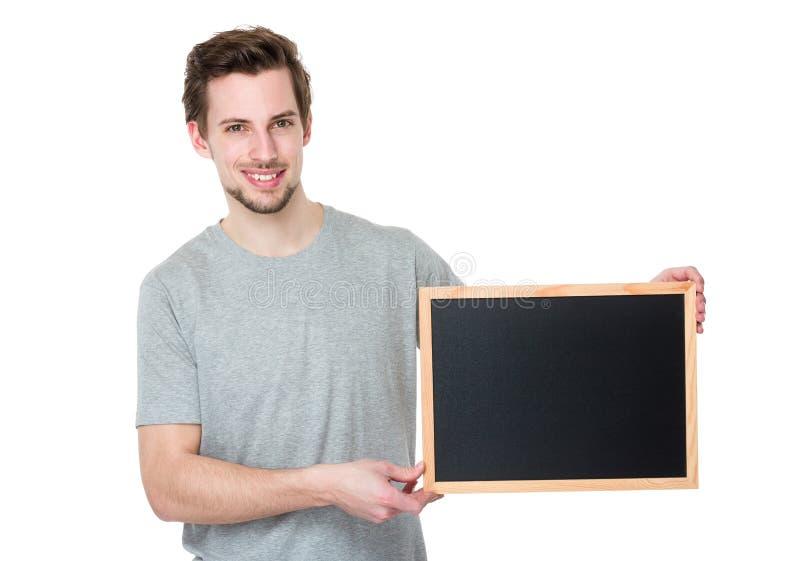 Homem ocasional novo que guarda um quadro-negro vazio fotos de stock