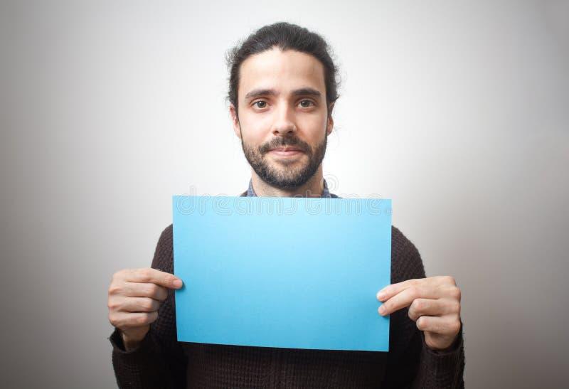Homem ocasional novo que guarda um sinal azul imagens de stock