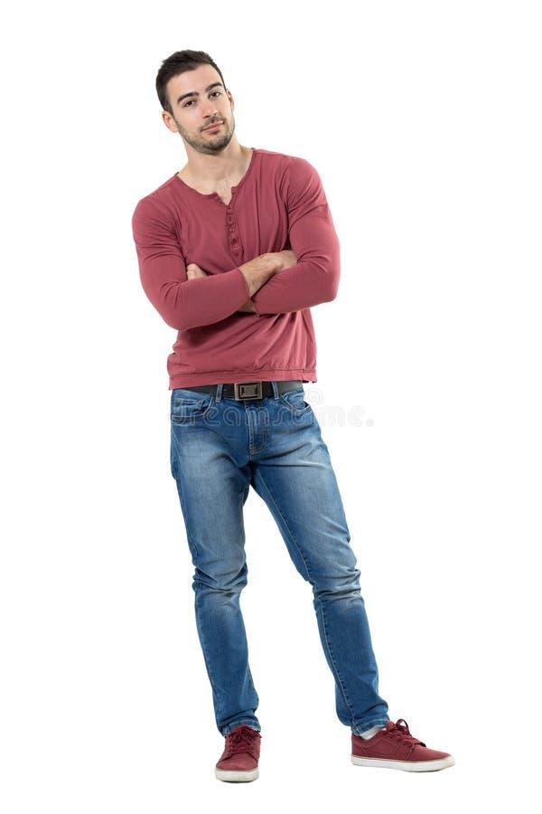Homem ocasional novo relaxado com os braços cruzados que inclinam e que olham a câmera imagens de stock royalty free