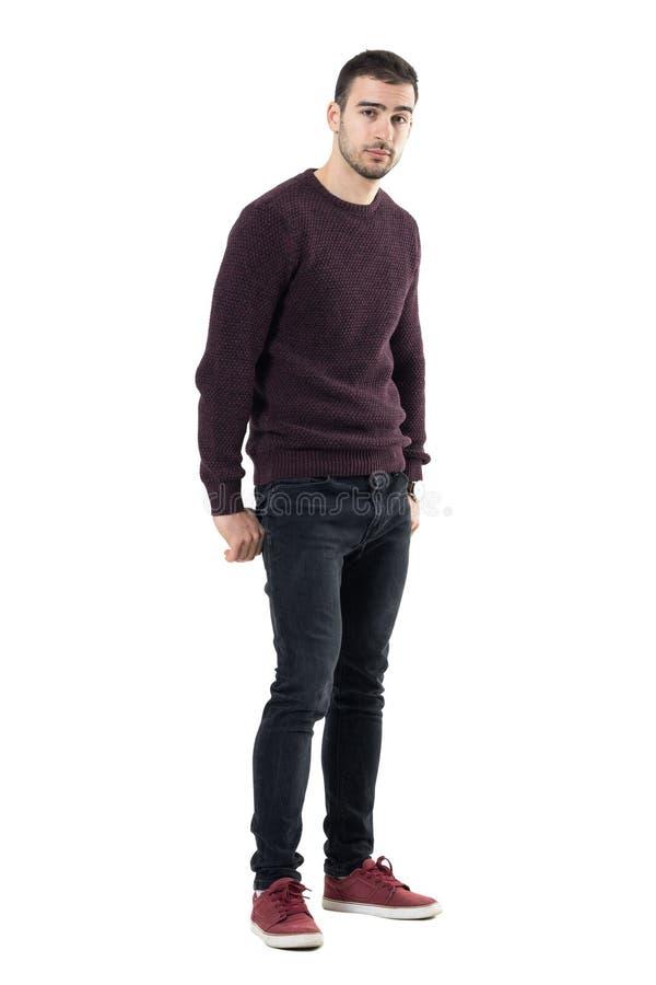 Homem ocasional novo sedutor fresco com mãos em uns bolsos traseiros que olham a câmera fotografia de stock
