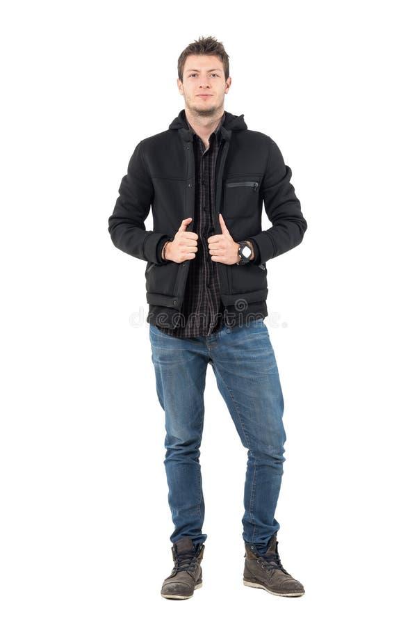 Homem ocasional novo seguro no revestimento preto encapuçado e nas calças de brim do inverno foto de stock royalty free