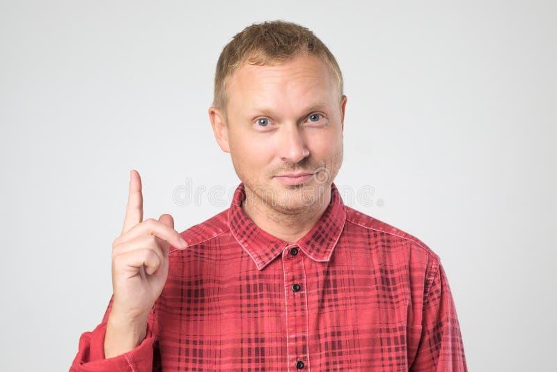Homem ocasional que aponta seu dedo acima que tem a ideia imagem de stock